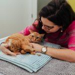 senhora a dar festinhas no seu gato num consultório veterinário